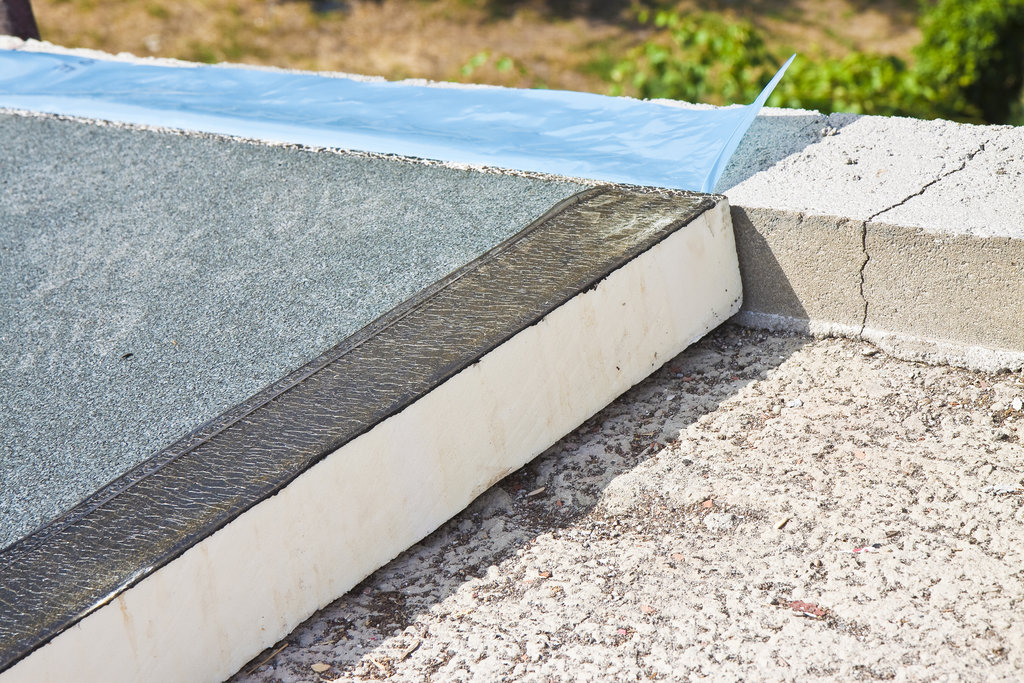 Roof thermal insulation with polystyrene panels covered with waterproof membrane under a concrete screed - Image with copy space