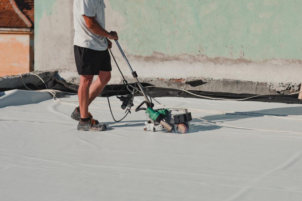 Worker welding pvc roof membrane by heater with welder machine