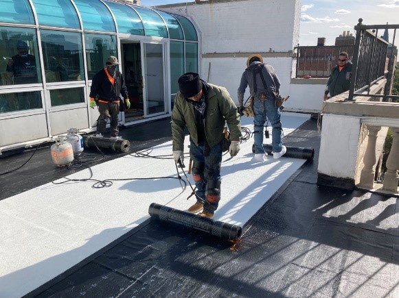 Reliable Roofing Technicians Rolling Out Mod Bit Roofing